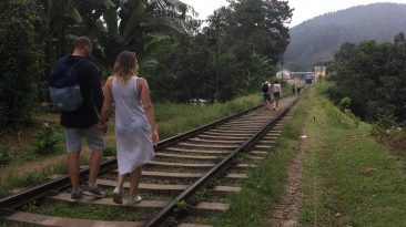 Tourist walking on train tracks in Ella