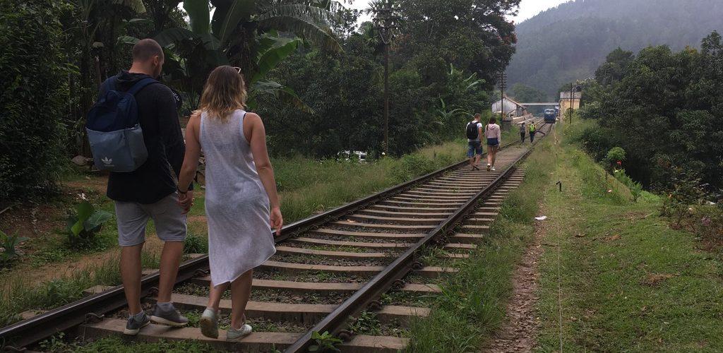 Tourist walking on train tracks in Ella